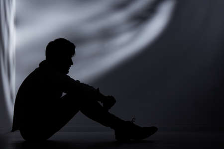 Abandoned man sitting on floor in dark room