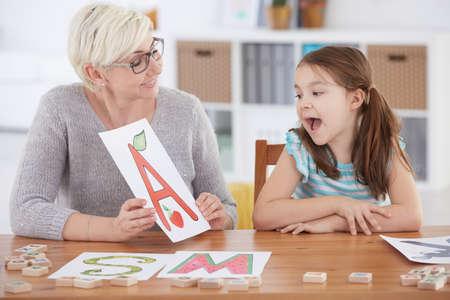 言語聴覚士が言語障害スペル手紙を持つ少女