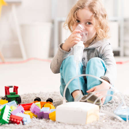 Small boy doing inhalation, sitting on a floor with toys in light interior