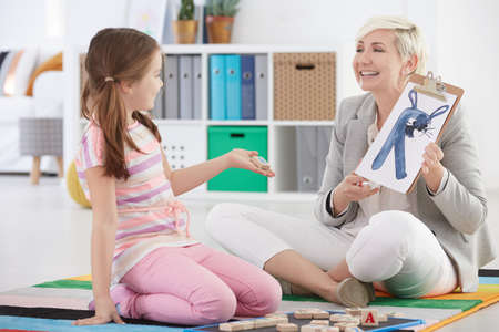 Girl studying difficult letters with speech therapist Stock Photo
