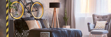 kingsize: King-size bed, grey armchair and black and yellow bicycle in modern bedroom