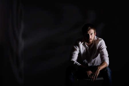 Verzweifelter Mann sitzt alleine in einem dunklen Raum Standard-Bild