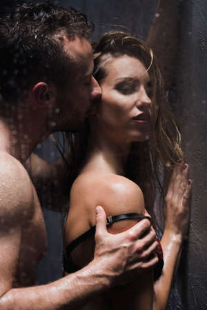Young couple kissing and having foreplay under the shower Stock Photo