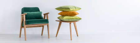 white pillow: Old green chair and wooden stool with pillows in white room