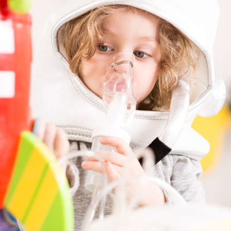 Child in an astronaut costume using a nebulizer, playing with a toy racket Stock Photo