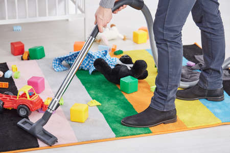 messy room: Close up of man vacuuming messy childs room Stock Photo