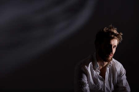Handsome, young man after nervous breakdown, dark background Stock Photo