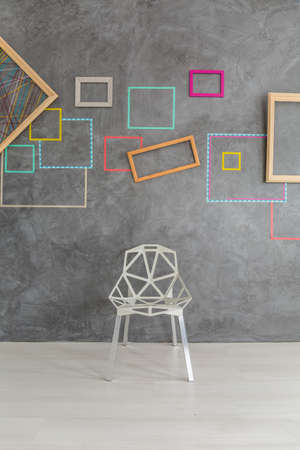 modern chair: Design modern chair in front of concrete wall with colorful frames