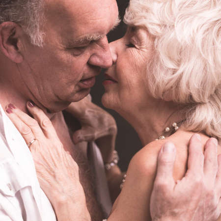 Senior sexy couple kissing softly during passionate moment in bedroom