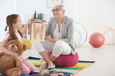 School pedagogue and girl learning by fun activities
