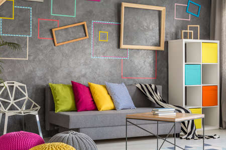 living room wall: Cozy living room with concrete wall with colorful frames