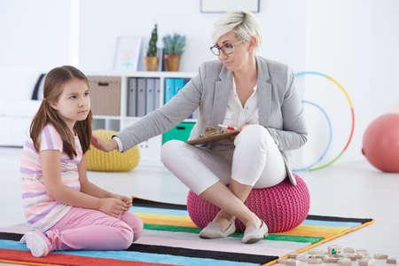 Child psychologist talking with sad school girl Stock Photo