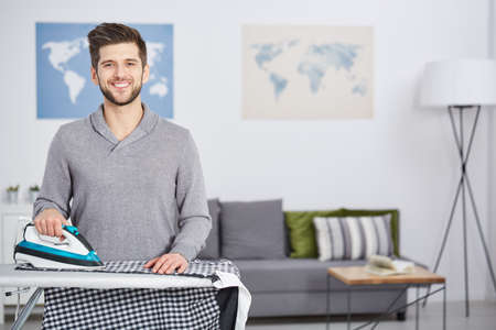 Happy, young man doing houseworks, ironing clothes