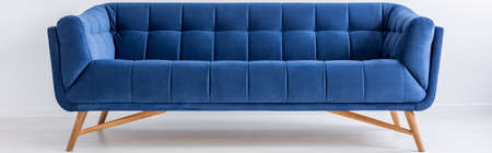 Blue modern sofa in room with white walls