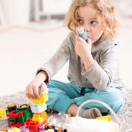 Small girl using inhaler device, playing with toys on a floor