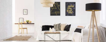 living room wall: White modern living room with big sofa and brick wall Stock Photo