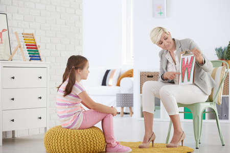 Girl with speech impediment learning reading difficult letters Stock Photo