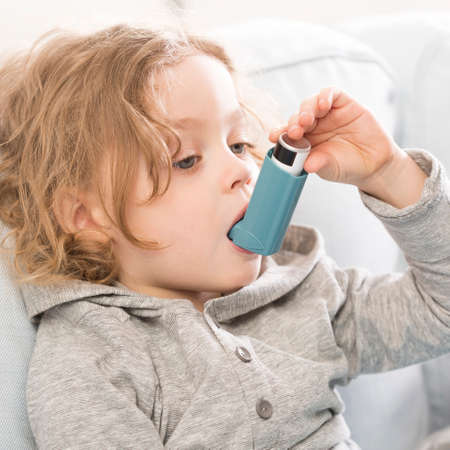 asthmatic: Small child using his inhaler device for asthma Stock Photo