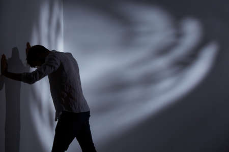 Beklemtoonde man die de muur stoot, staand in een donkere kamer