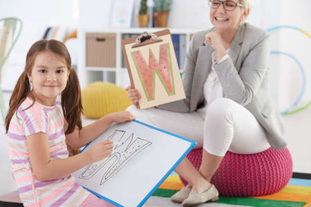 Girl with speech disorder during therapy with specialist