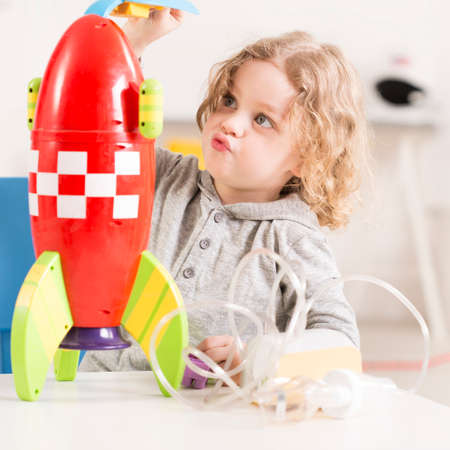 inhalation: Child playing with toy racket, inhaler device lying on a table