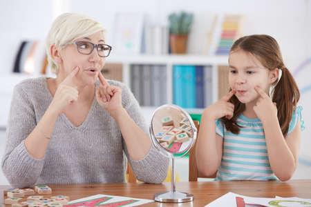 educadores: Chica con impedimento del habla ejercicio con el terapeuta Foto de archivo
