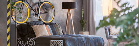 King-size bed in dark hipster bedroom with a bicycle on a wall