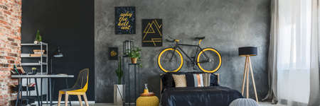 yellow walls: Hipster studio apartment with grey and brick walls and yellow accessories