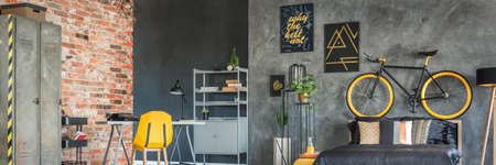 Creative grey and yellow bedroom design with bike and posters on the wall Stock Photo