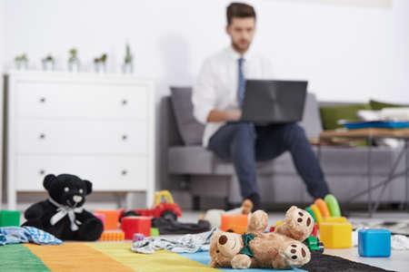 padre de negocios con la computadora portátil que trabaja en la habitación desordenada
