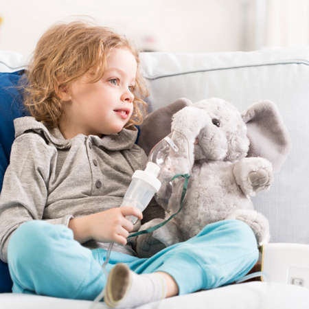 Little child sitting on a sofa with an elephant toy with oxygen mask Stock Photo