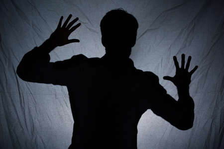 scarry: Scarry shadow of man standing behind dark fabric Stock Photo