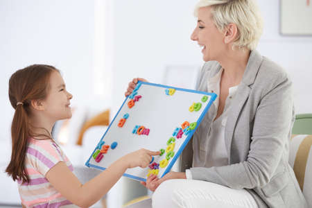 Happy girl learning alphabet with private tutor
