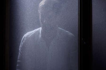 夜に汚れた窓の後ろに立って孤独な男