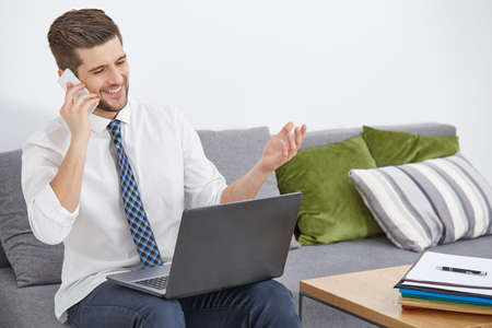 Content man with laptop and phone working at home
