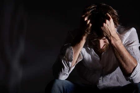 Człowiek cierpi ból emocjonalny, trzymając głowę w dłoniach Zdjęcie Seryjne