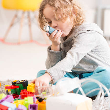 Small boy with asthma using inhaler, sitting on a floor playing toys Stockfoto