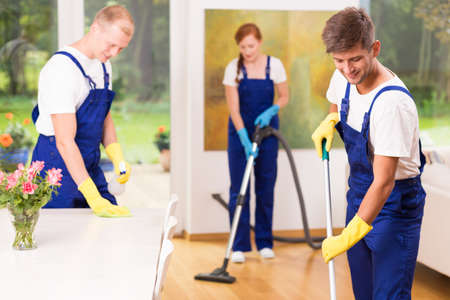 dungarees: Professional cleaning team is vacuuming the living room