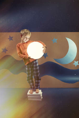 star sky: Boy in pajama standing on books and holding the lighting ball
