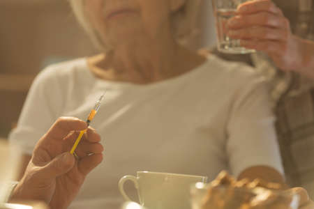 Close-up of syringe with medicine for sick elderly woman Stock Photo