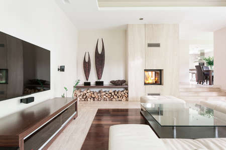 lightsome: Part of spacious white living room with glass table, fireplace and TV set
