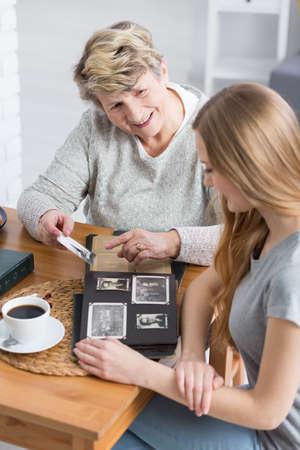 Feliz abuela mostrando fotos viejas a su nieta Foto de archivo - 73045667