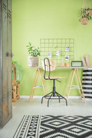 Green home office with desk, chair and old metal wardrobe