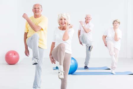 Groep actieve senioren die op de sportschool uitoefenen en glimlachen