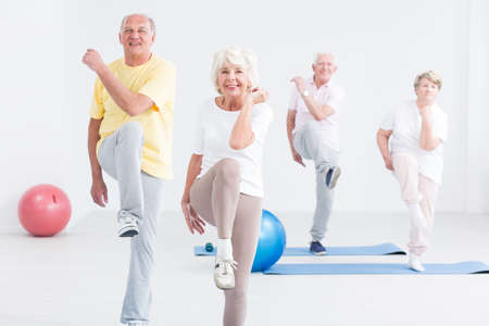 Group of active seniors exercising at the gym and smiling Stock Photo