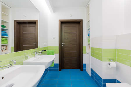 Modern bathroom with blue floor, large mirror and two sinks