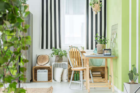 Green study area with striped window curtain, plants and desk