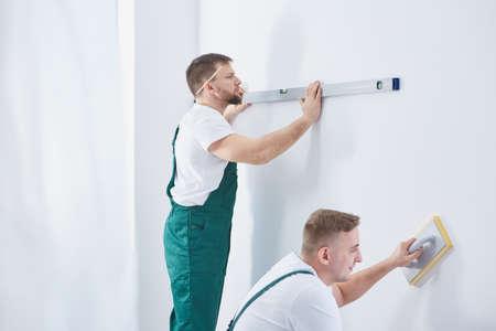 Zwei professionelle Männer zusammen zu Hause Renovierung arbeiten