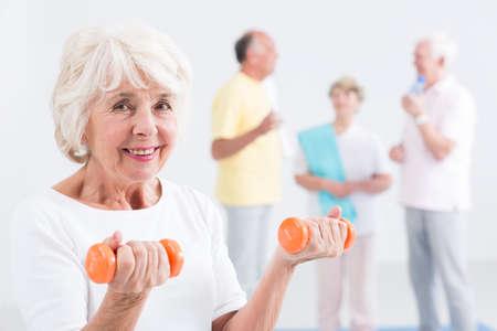 ジムで小さい dumbbels を保持している幸せの年配の女性 写真素材