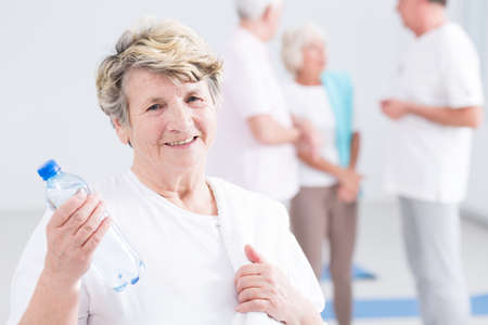 haciendo ejercicio: Sonriente mujer senior con botella de agua en el gimnasio Foto de archivo